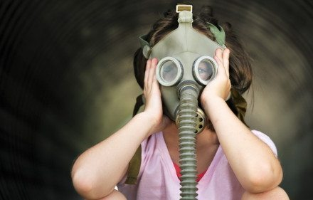 Young girl dons a gas mask.